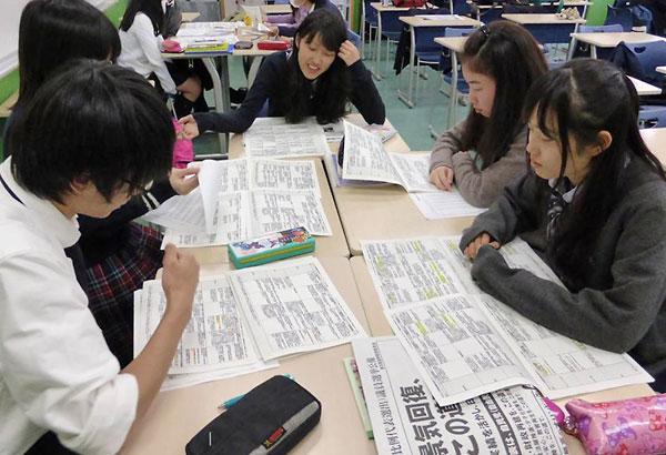 模擬選挙の前に政策を比較する高校生