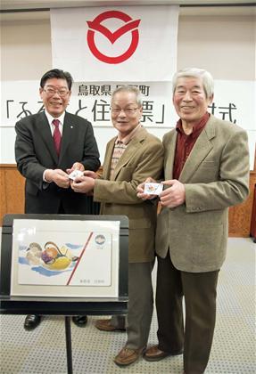 2月22日の交付式で、日野町出身の2人にカードを進呈する景山享弘町長