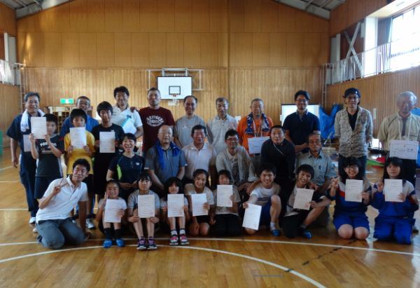 南小体育館で大人たちと一緒に記念撮影する小中学生