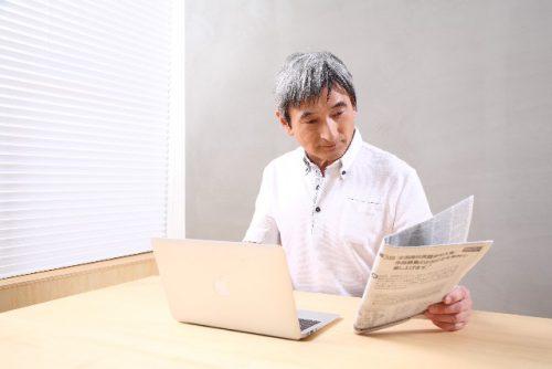 パソコンと新聞を見る男性