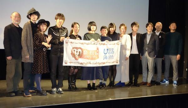東京会場のステージで、そろって写真撮影に応じる上映会関係者