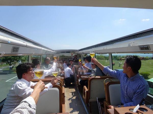 走行中のバスの車内で乾杯する乗客ら