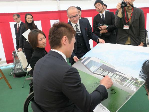 完成予想図にサインする島川、添田両選手