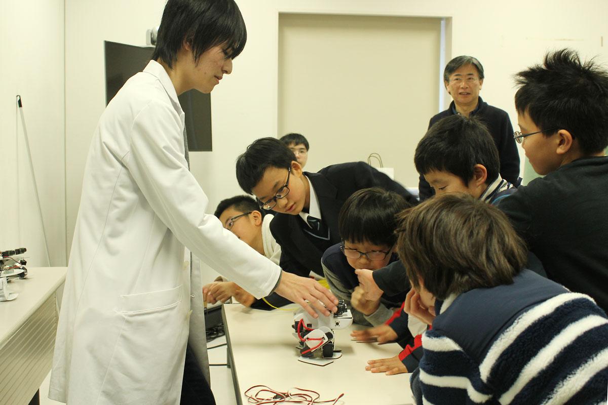 ロボットの説明をする鳥山さんと興味津々の子どもたち