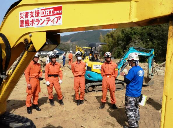 重機のそばで指導を受ける福岡市消防局の消防重機隊員4人。説明するのは日本財団災害支援チームの黒澤司(右)=3月30日