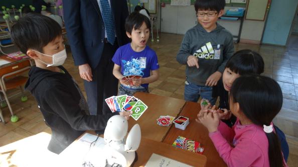 昼休みにオリヒメ(正面手前)を通じて院内学級の児童とトランプゲームをして遊ぶ級友たち