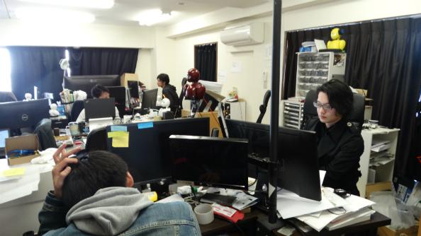 オリヒメが置かれた事務所で仕事をする吉藤オリィ研究所代表(右端)