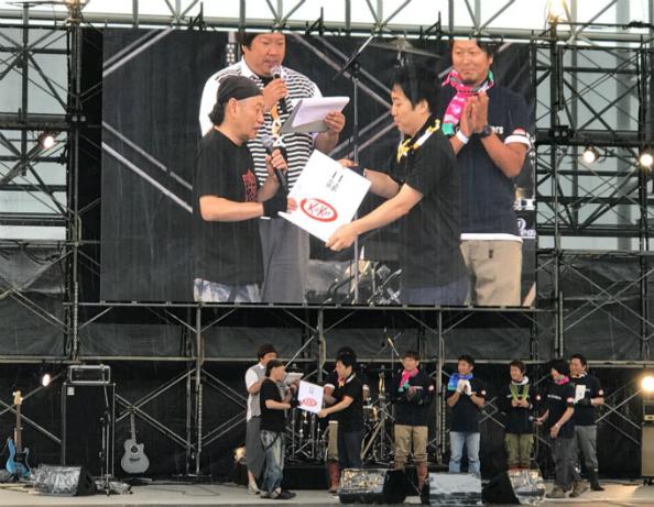 ネスレ日本の槇部長(右から2人目)から寄付金の目録を受け取る泉谷さん
