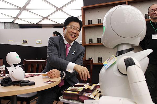 視察に訪れた加藤氏にお菓子を運ぶオリヒメディー。テーブルの上はオリヒメ
